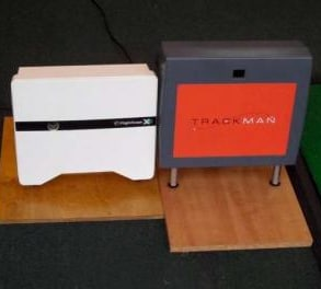 Photo showing a FlightScope golf launch monitor beside a TrackMan golf radar.