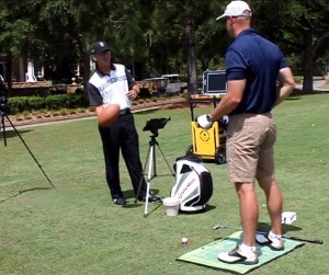 Photo showing Rob Strano using a FlightScope launch monitor and the BodiTrak Pressure Mat to analyze the player's stance and swing.